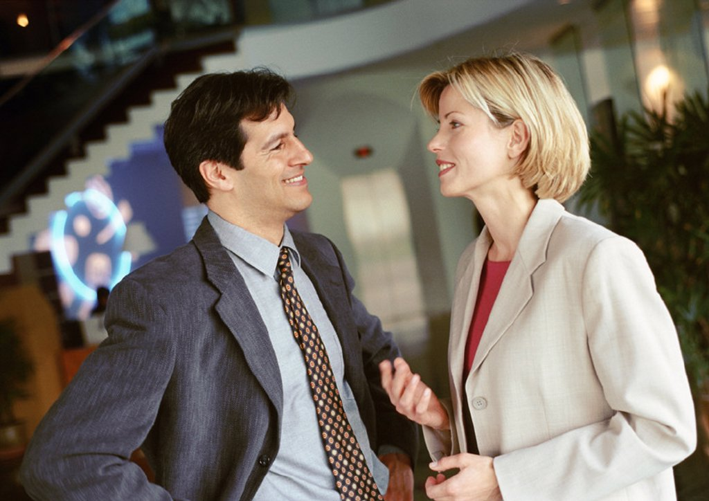 Businessman and businesswoman standing face to face, smiling : Stock Photo