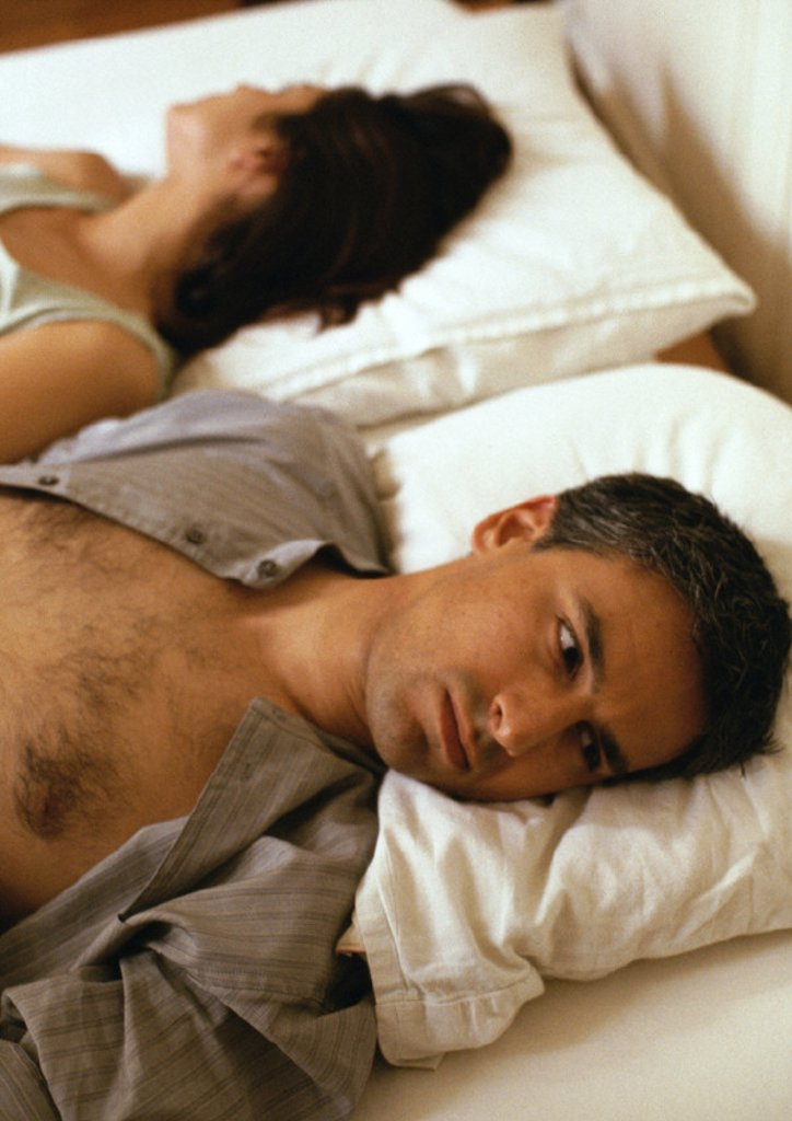 Man and woman lying in bed, heads on pillows, facing opposite directions, head and shoulders : Stock Photo