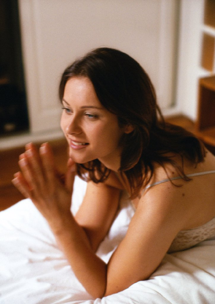 Woman propped up on elbows on bed with hands together, close-up, blurred motion : Stock Photo