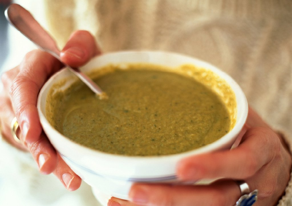 Hands holding bowl of leek soup, close-up : Stock Photo