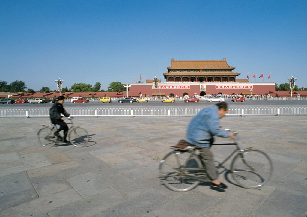 Stock Photo: 1569R-49034 China, Beijing, two people riding bicycles in street in front of The Forbidden City