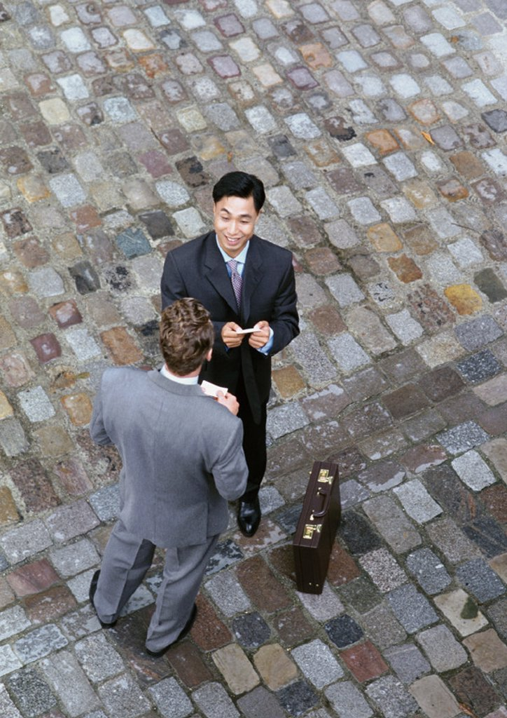 Two men standing face to face on cobblestones, elevated view : Stock Photo