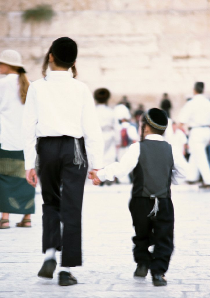 Israel, Jerusalem, two Orthodox Jewish boys wearing kippas and holding hands, rear view : Stock Photo