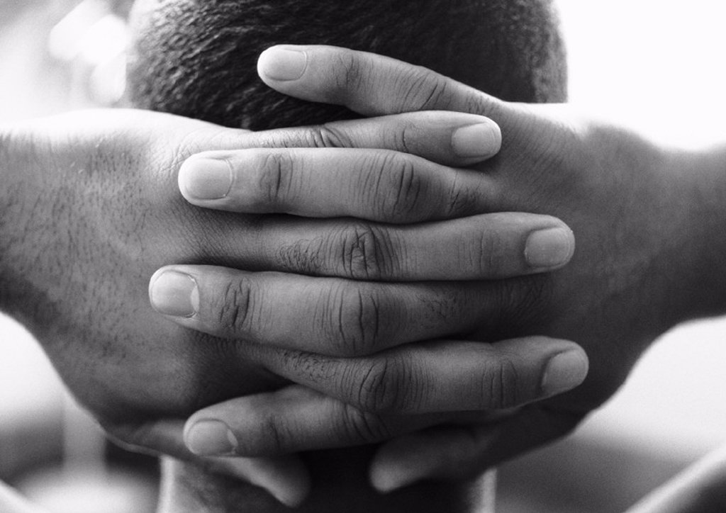 Man´s hands clasped behind head, close-up, b&w : Stock Photo