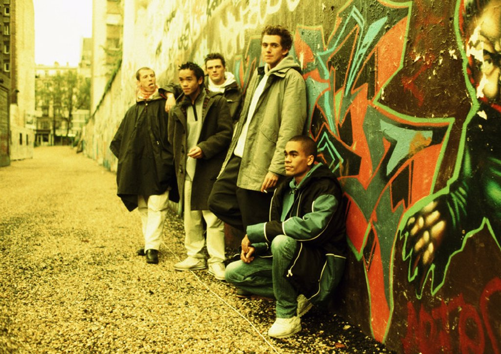 Five young men leaning against wall covered in graffiti, full length : Stock Photo