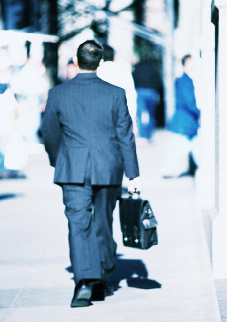 Businessman walking in street, rear view : Stock Photo