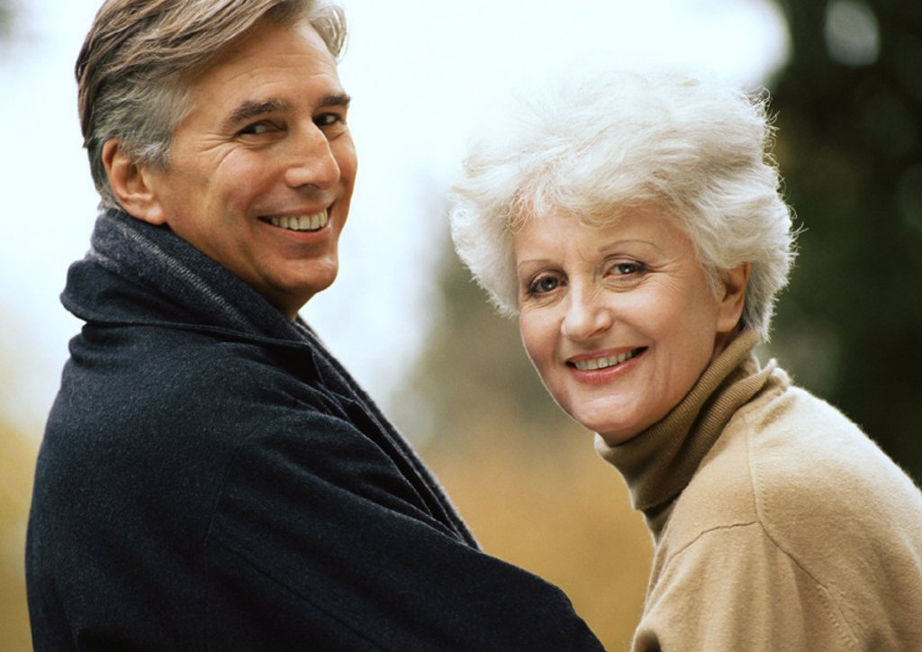 Man and woman smiling over shoulders into camera, close-up : Stock Photo