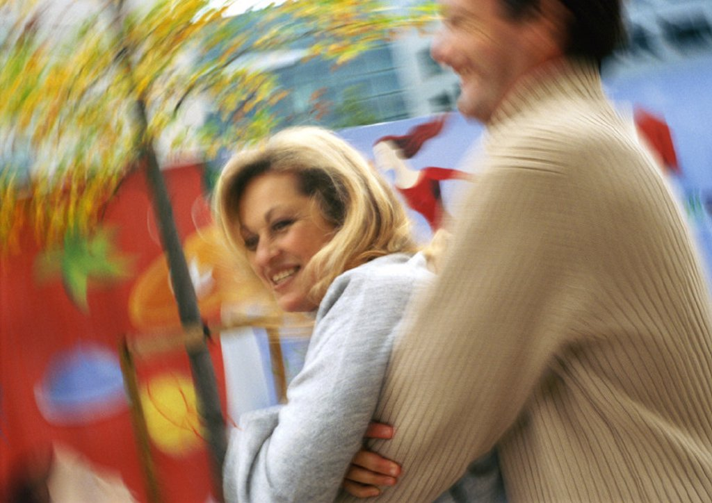 Man holding woman from behind, side view, motion, blurred : Stock Photo