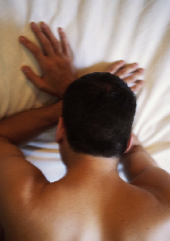 Stock Photo: 1569R-67074 Man lying face down on bed with head on hands, blurred, high angle view