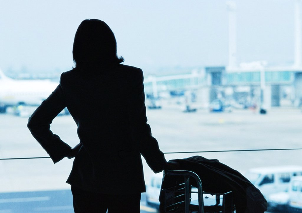 Businesswoman next to luggage, silhouette, airplanes in background : Stock Photo