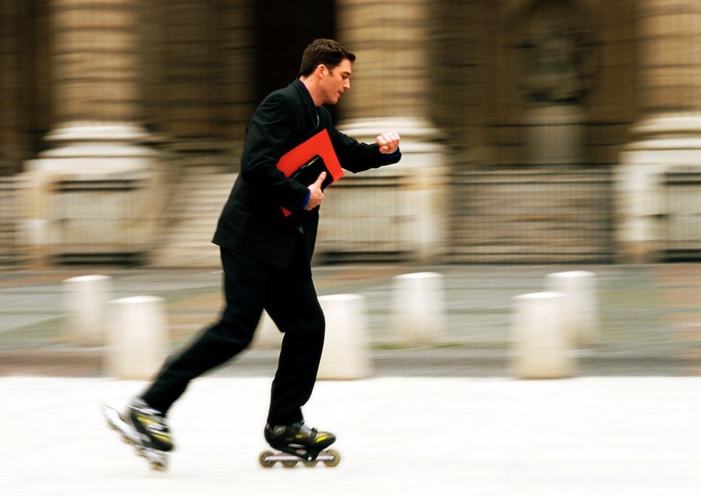 Stock Photo: 1569R-69034 Businessman rollerblading in front of building and checking time, blurred