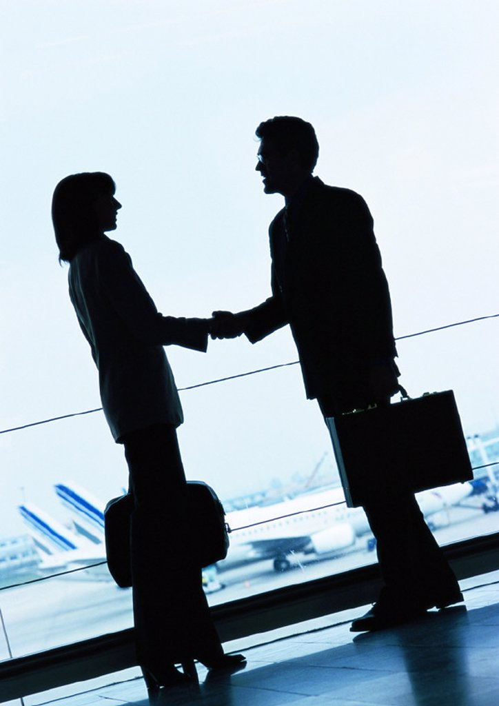 Businessman and businesswoman shaking hands in airport, silhouette : Stock Photo
