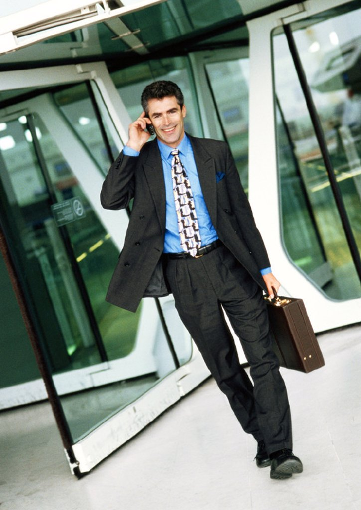Stock Photo: 1569R-69056 Businessman using cell phone, walking away from glass doors, full length