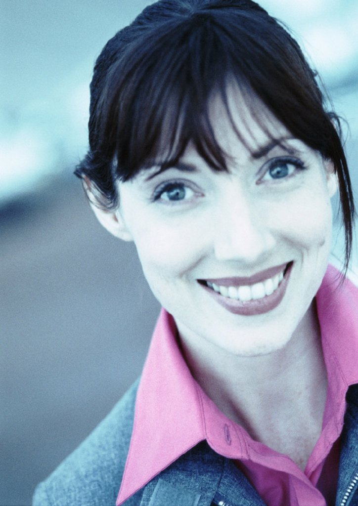 Businesswoman smiling at camera, close-up, portrait, cool-toned : Stock Photo