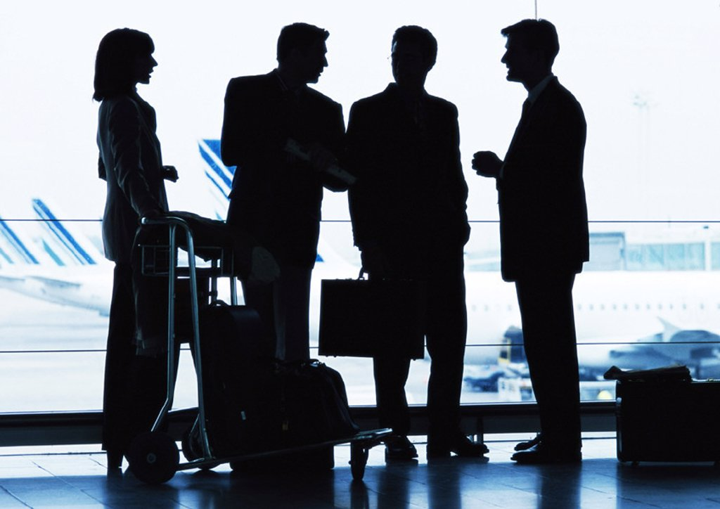 Group of business people standing inside airport, silhouette : Stock Photo