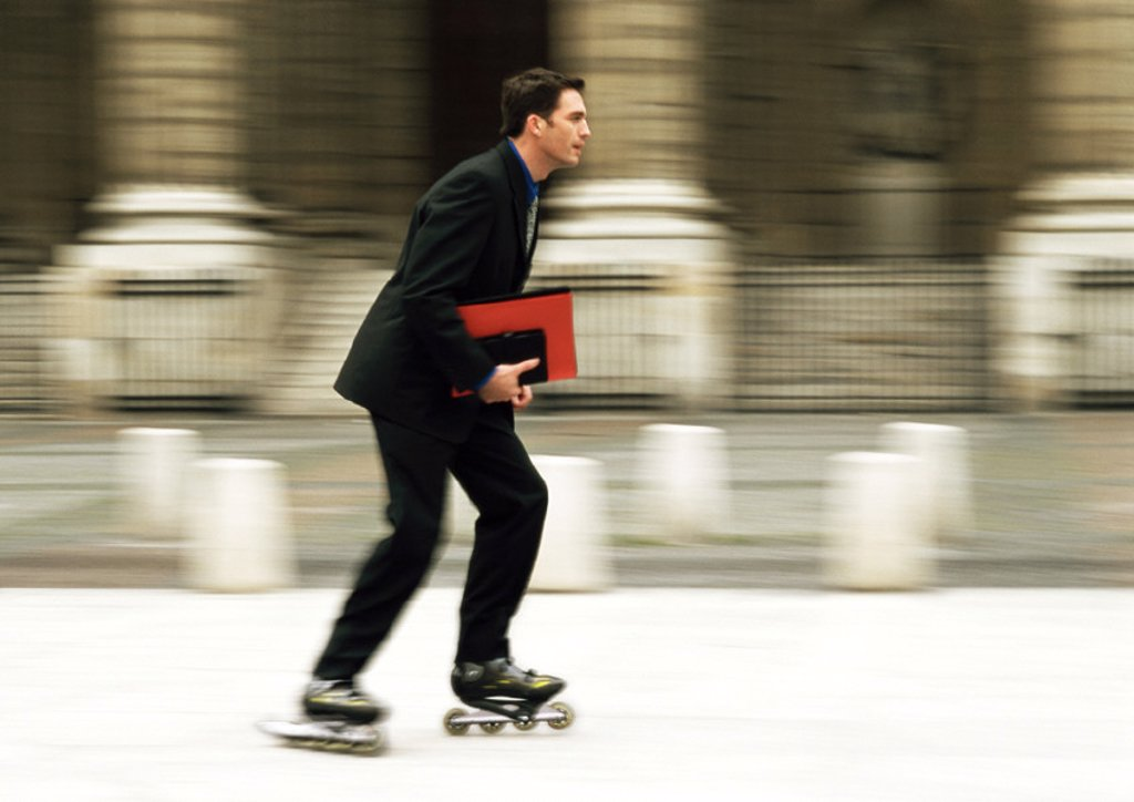 Stock Photo: 1569R-69069 Businessman rollerblading in front of building, blurred