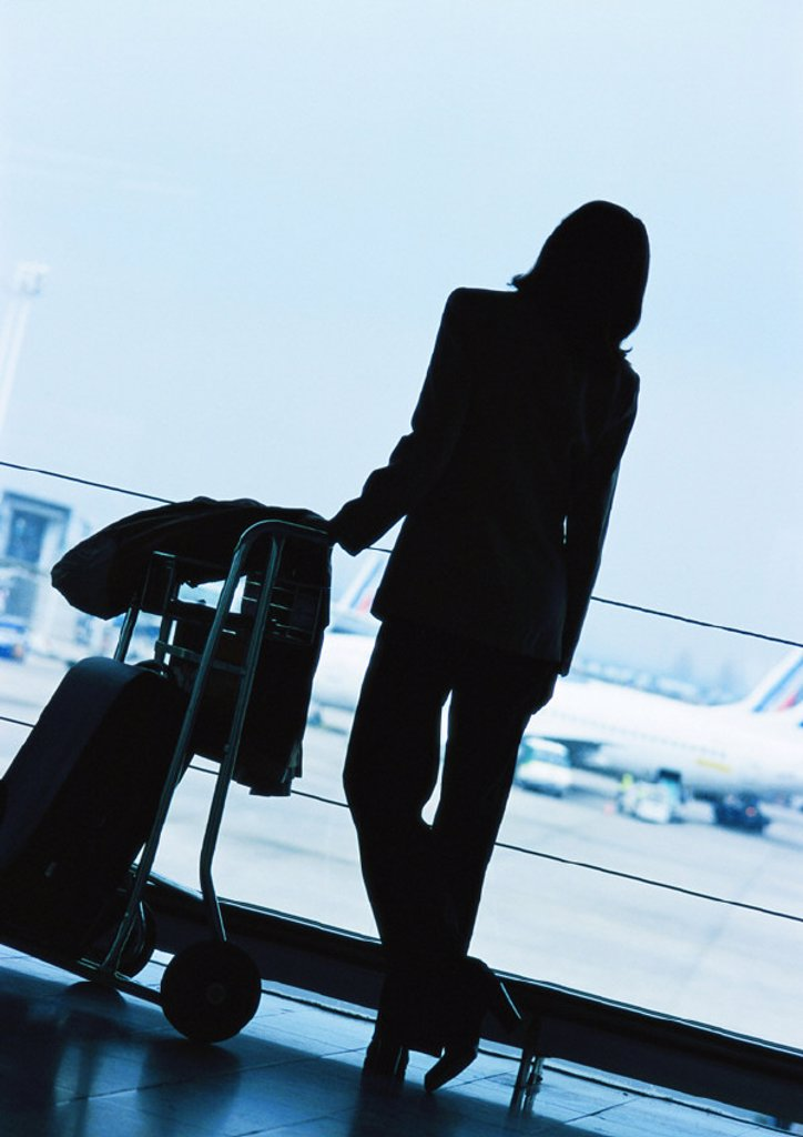 Businesswoman standing next to luggage in airport, silhouette : Stock Photo