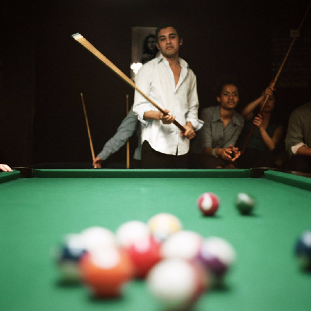 Stock Photo: 1569R-70041 Young man shooting pool, people watching in background, billiard balls blurred in foreground