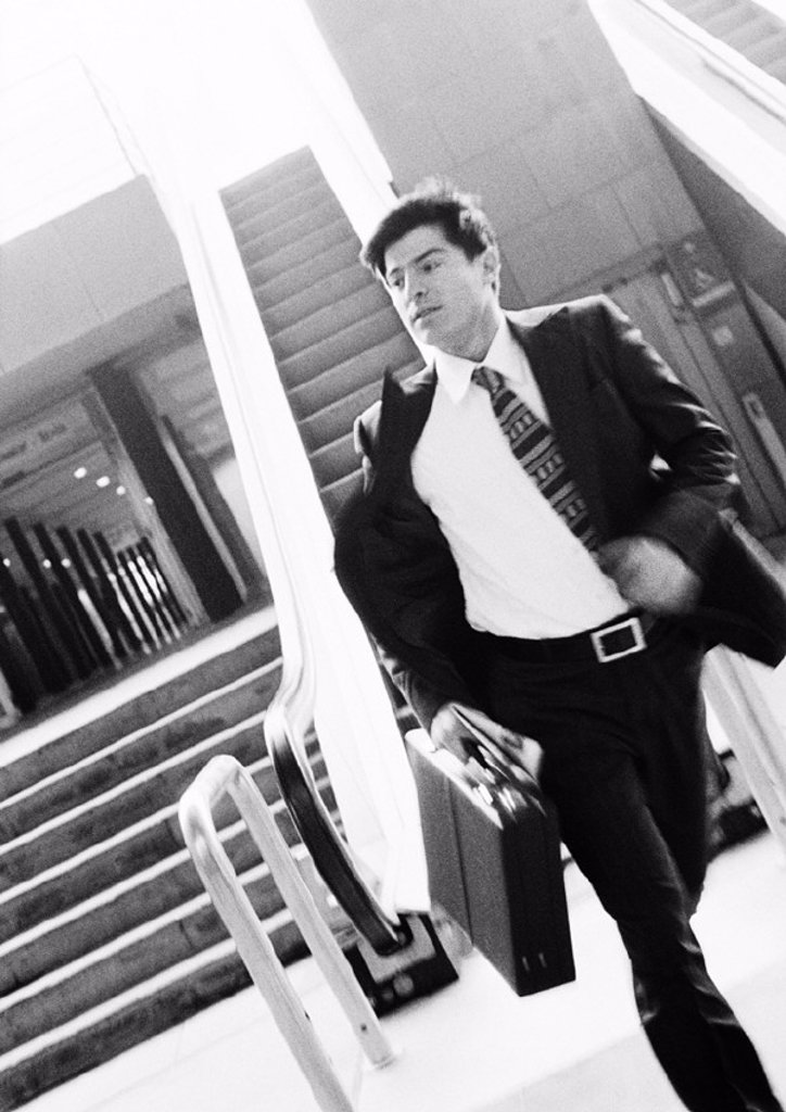 Stock Photo: 1569R-71029 Businessman hurrying away from escalator, holding briefcase, blurred motion, b&w