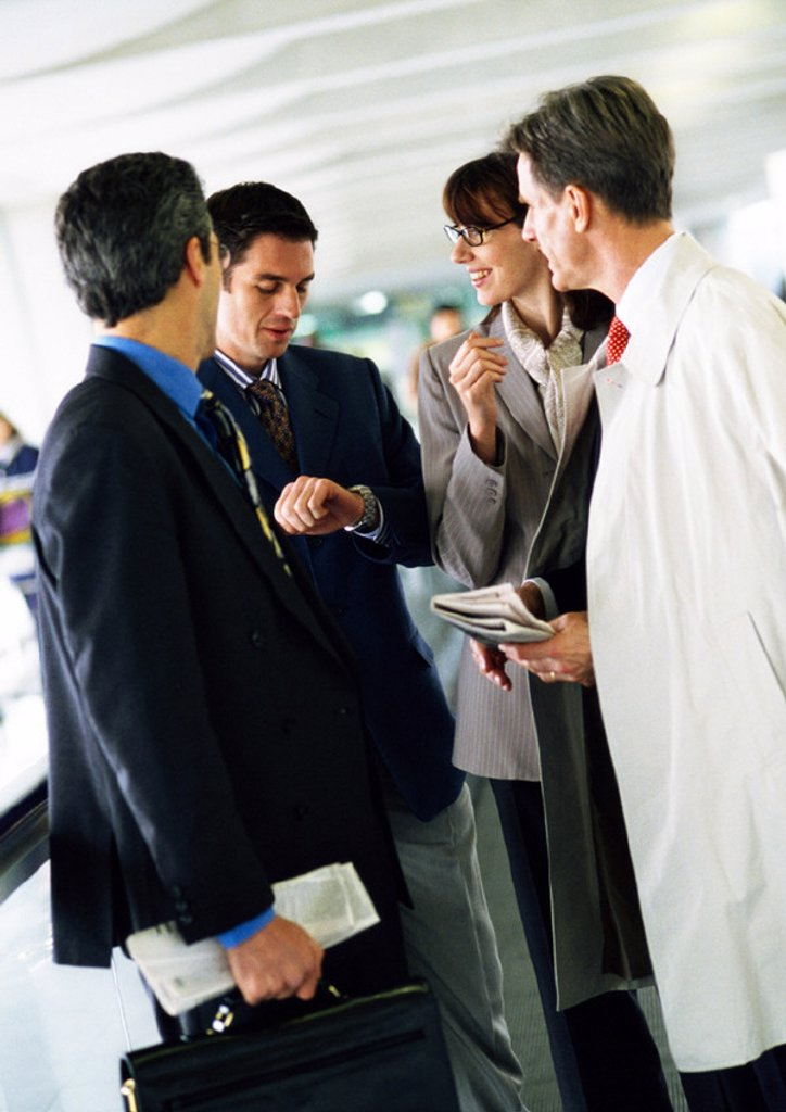 Business people standing together, one looking down at watch : Stock Photo