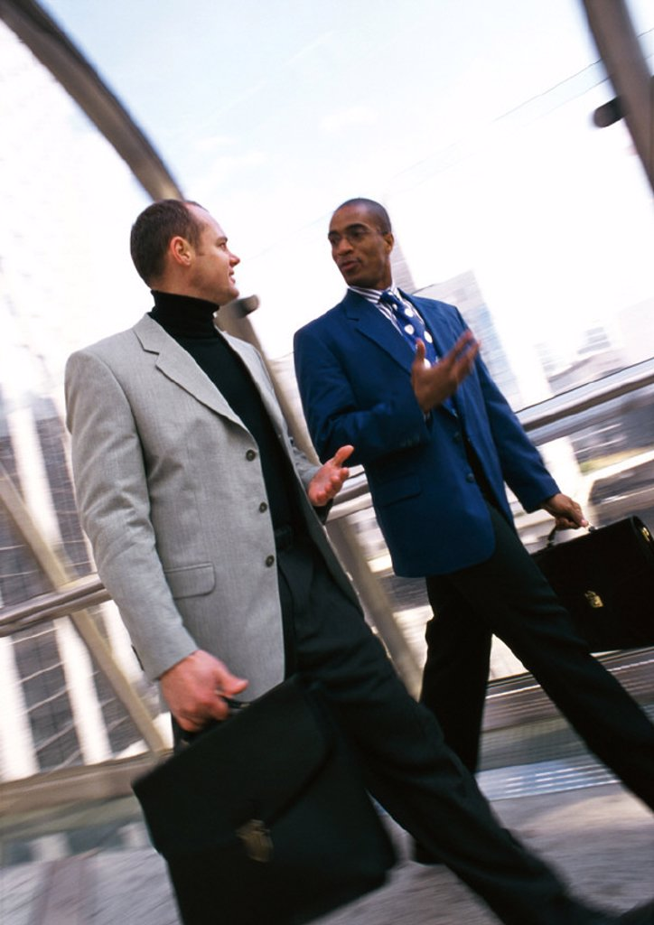 Stock Photo: 1569R-71078 Businessmen walking together in elevated passageway, bulidings in background