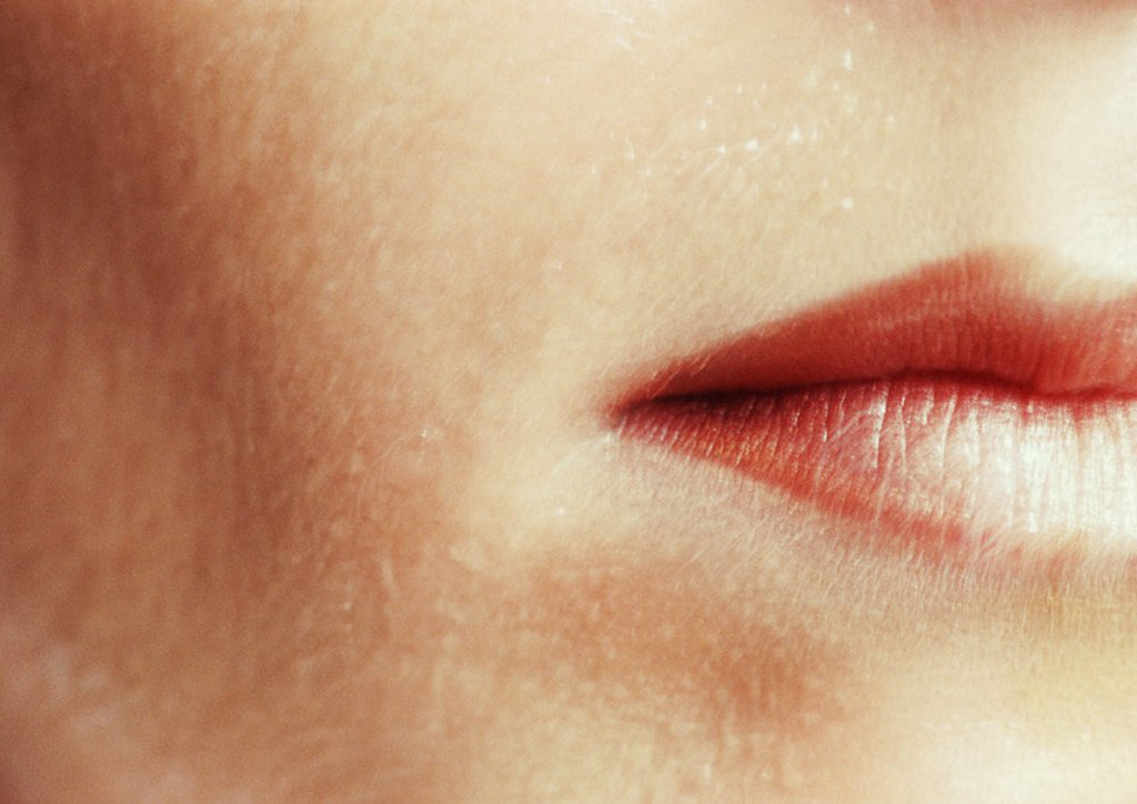 Woman wearing lipstick, close up of cropped mouth : Stock Photo