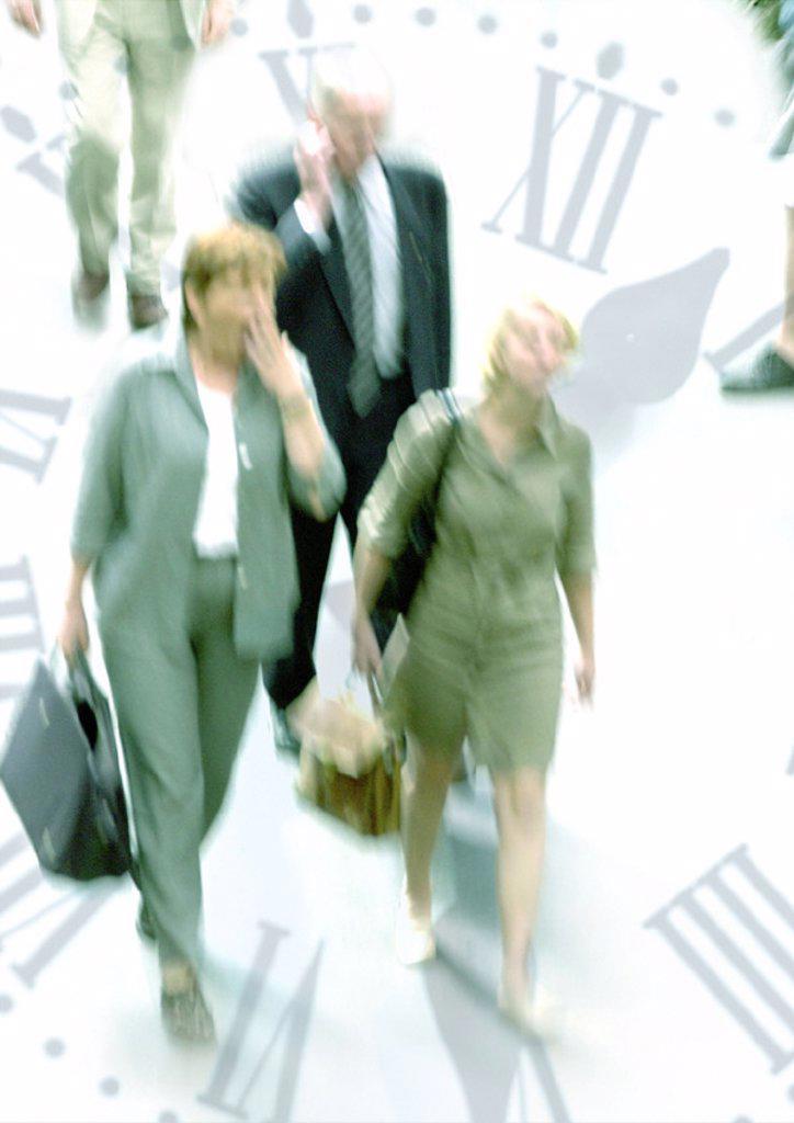 Businesspeople walking through clock, montage : Stock Photo