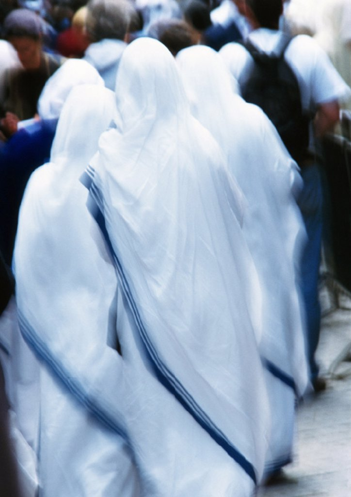 Stock Photo: 1569R-81043 Israel, Jerusalem, nuns clothed in white looking toward crowd, rear view, blurry