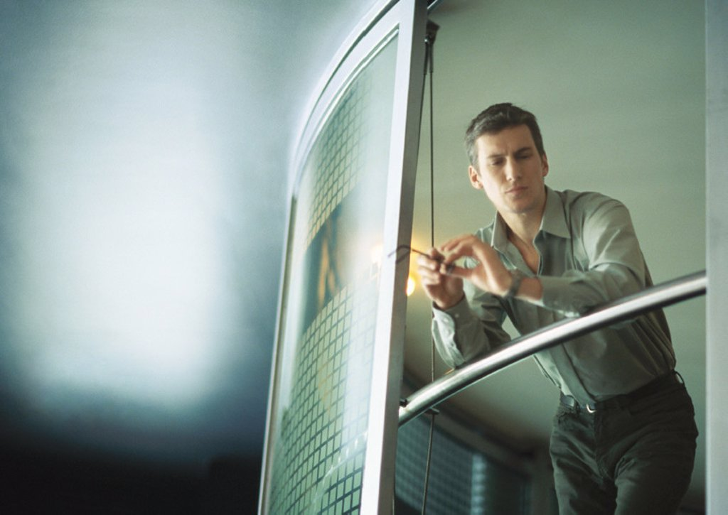 Stock Photo: 1569R-9010057 Businessman leaning on rail, low angle view