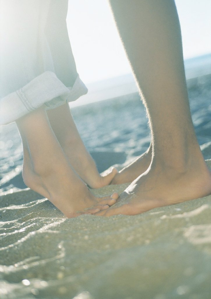 Stock Photo: 1569R-9010223 Teenage couple, girl standing on tiptoes, close-up of lower legs and feet