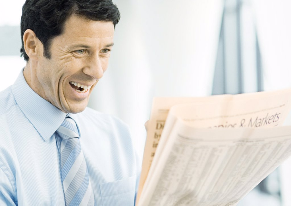 Stock Photo: 1569R-9010506 Businessman looking at newspaper excitedly