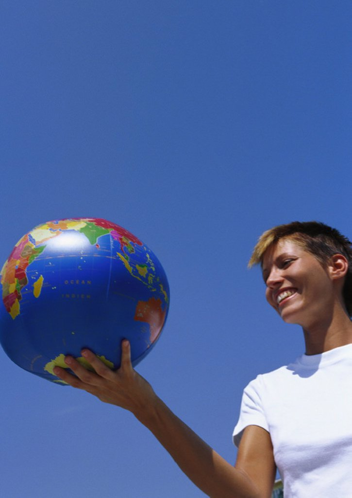 Stock Photo: 1569R-9010778 Young woman holding globe ball