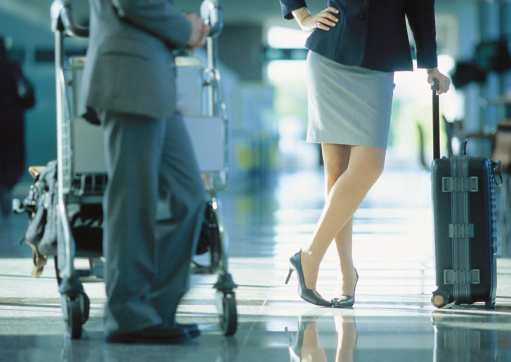 Businessman and businesswoman standing with luggage in airport : Stock Photo