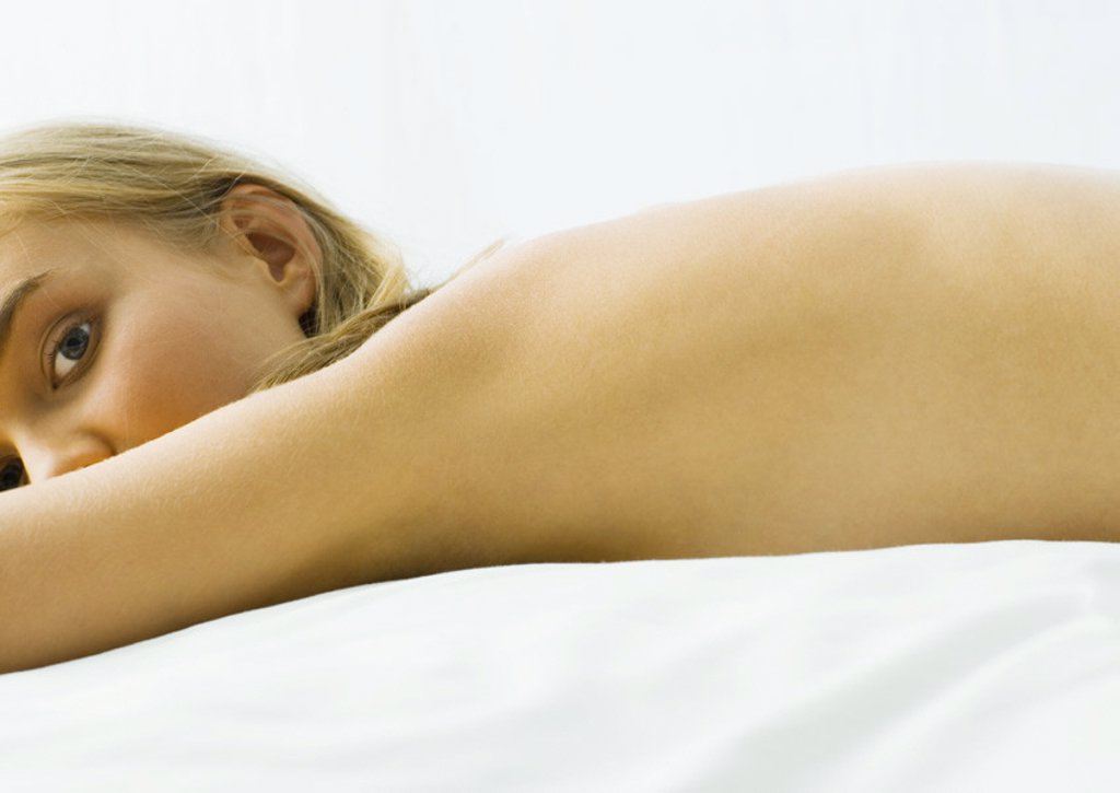 Young woman lying on bed nude : Stock Photo