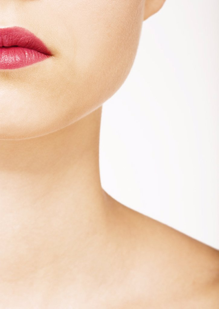 Woman wearing lipstick, view of lower face and neck : Stock Photo