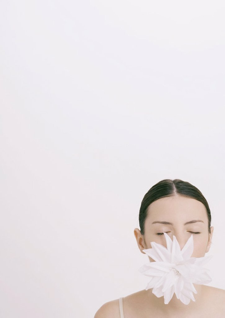 Woman with flower in mouth and eyes closed : Stock Photo
