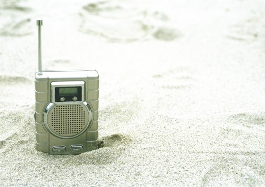 Stock Photo: 1569R-9011283 Radio sticking out of sand on beach