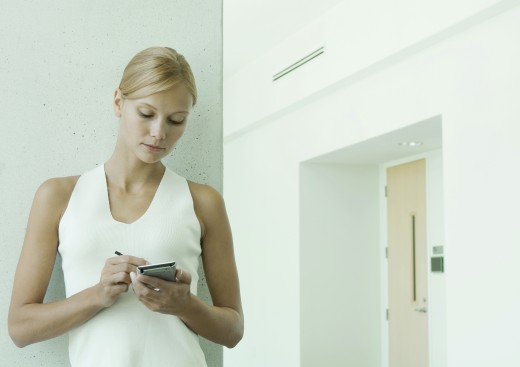 Woman using electronic organizer in hallway of office building : Stock Photo