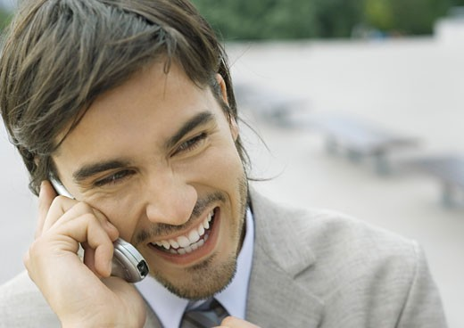 Young businessman using cell phone and laughing : Stock Photo