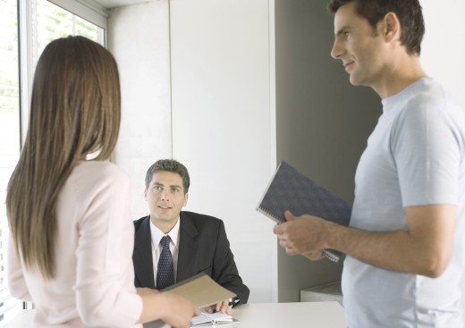 Couple speaking to businessman in office : Stock Photo