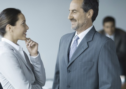 Business colleagues standing face to face, smiling : Stock Photo