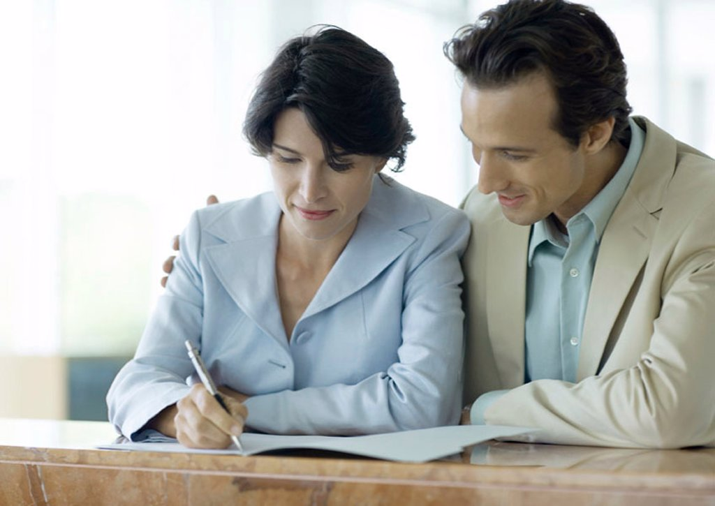 Stock Photo: 1569R-9012779 Couple signing document at counter