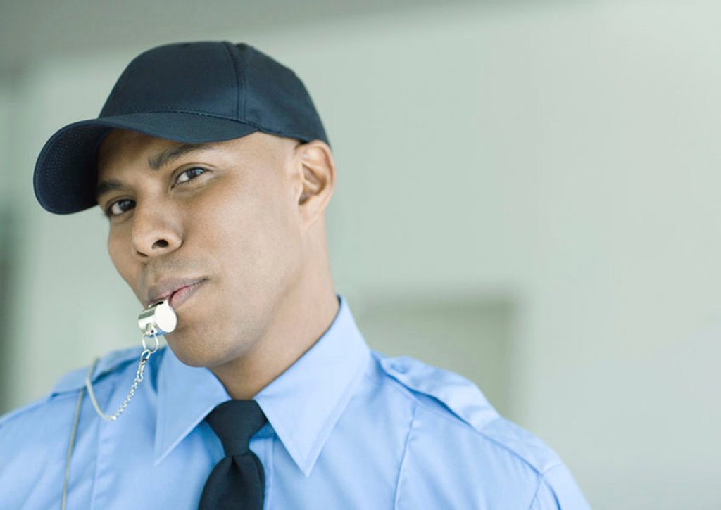 Security guard blowing whistle : Stock Photo