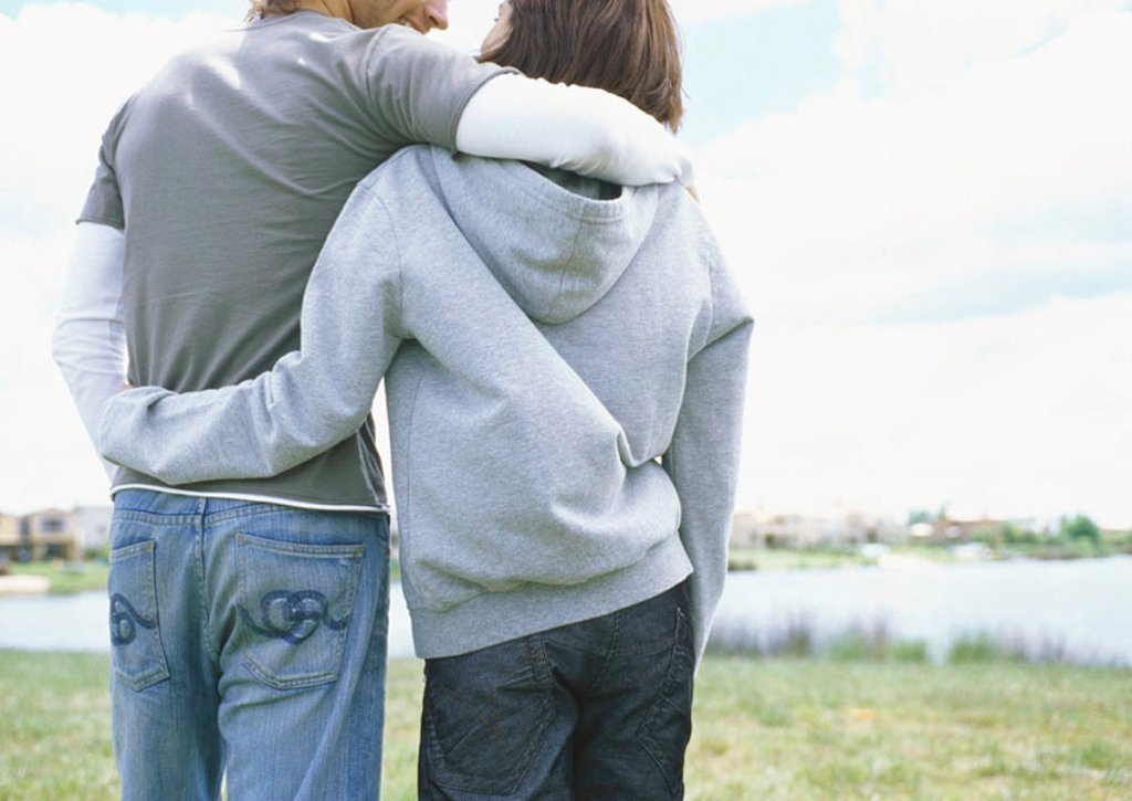 Stock Photo: 1569R-9013582 Young couple walking outdoors, rear view
