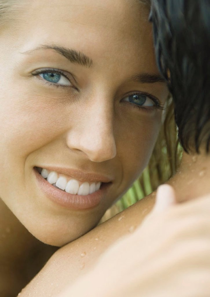 Woman embracing man, smiling at camera : Stock Photo
