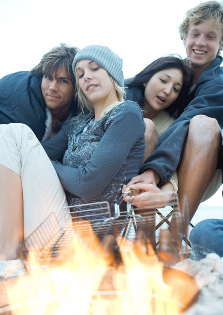 Young adults grilling hotdogs over campfire : Stock Photo
