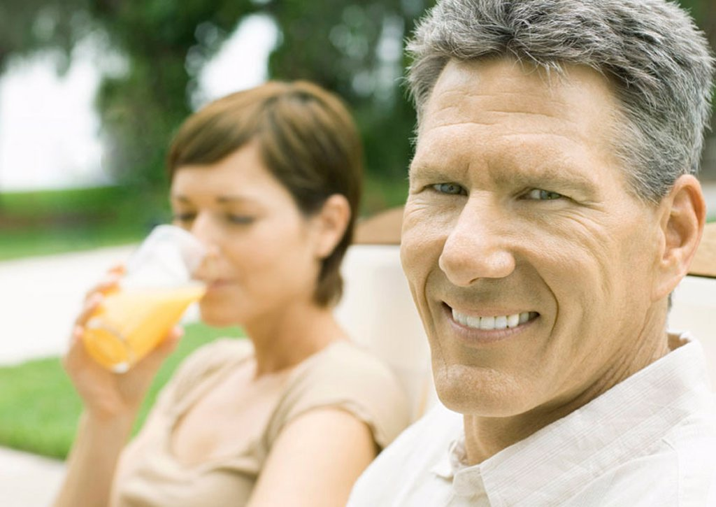 Man smiling as woman drinks juice in background : Stock Photo