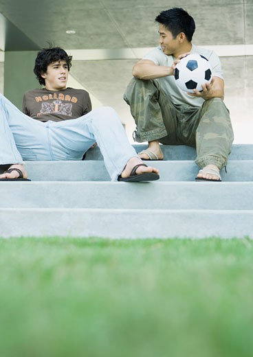 Two male college students sitting on steps, talking : Stock Photo