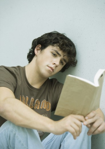 Young man reading book : Stock Photo