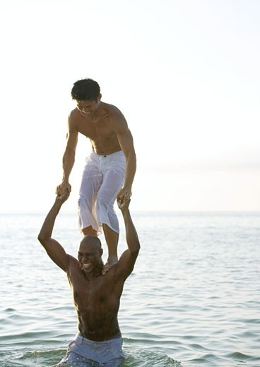 Stock Photo: 1569R-9014600 In sea, man standing on second man's shoulders